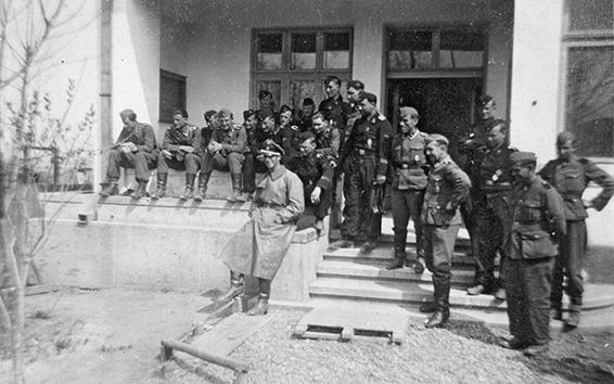 Kompanie personnel assemble outside the rail station in Bacau, April 1944. Standing on the steps in field-grey uniform at the bottom of the steps is the Kompanie Spieß, with Beneke next to him.