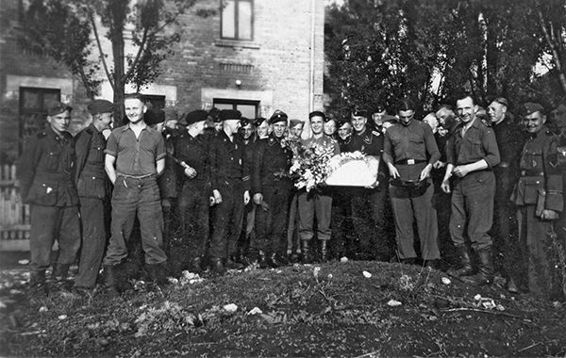 Officers and men from 9. Kompanie gather to celebrate Mother's Day in Bacau on 14 April 1944. The man in the center holding the bouquet of flowers is Beneke, Kompanie Spieß (roughly equivalent to master sergeant).